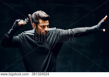 Warrior Fighter With A Sword And Shuriken Ready To Stab Enemy Over Black Background. Japanese Fighte
