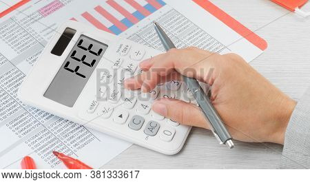 Fee Text On A Calculator With Financial Data Paperwork On The Desk. Business And Finance Fee And Reg