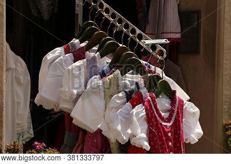 Dirndl Dresses Of Various Colors Hanging A Rack