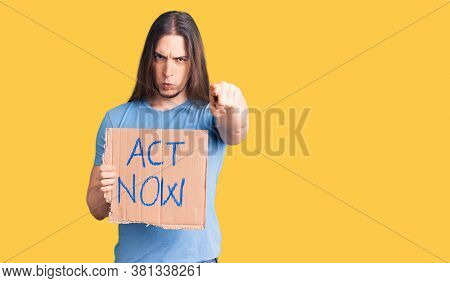 Young adult man with long hair holding act now banner pointing with finger to the camera, confident gesture looking serious