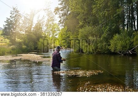 fly fisherman in summer fishing in a mountain river with waders and a cap