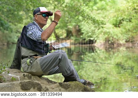 fly fisherman in summer choosing his fly for dry fly fishing