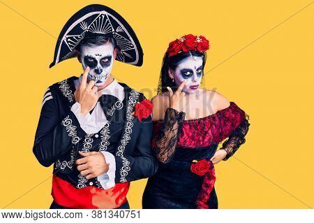 Young couple wearing mexican day of the dead costume over background pointing to the eye watching you gesture, suspicious expression