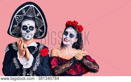 Young couple wearing mexican day of the dead costume over background clapping and applauding happy and joyful, smiling proud hands together