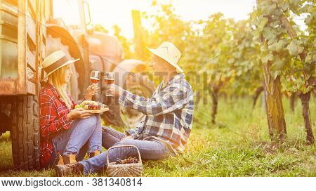 Couple having a romantic picnic with wine tasting in the vineyard in autumn