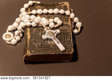 Old Religious Book With A Rosary And White Crucifix On Top On Dark Background