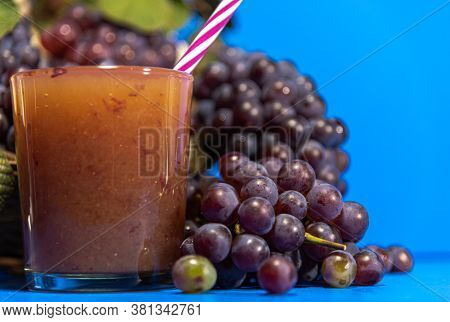 Niagara Grape Juice And Bunches (vitis Labrusca 'niagara') On Blue Background