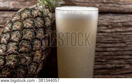 Natural Juice And Fresh Fruits Of Pineapple (ananas Comosus) On Woody Background