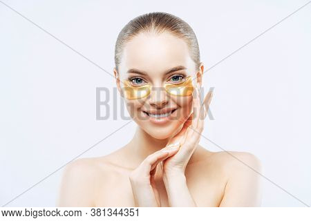 Studio Shot Of Attractive European Woman Touches Face Gently, Smiles Tenderly, Applies Golden Hydrog