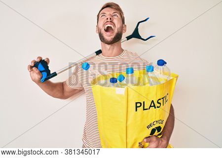 Young caucasian man holding recycling bag with plastic bottles and waste picker angry and mad screaming frustrated and furious, shouting with anger looking up.