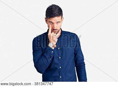 Young handsome man wearing casual shirt pointing to the eye watching you gesture, suspicious expression