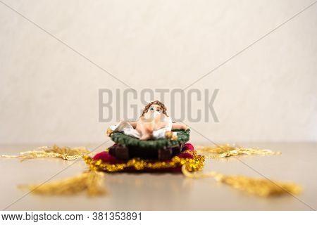 Image Of Baby Jesus Lying In Nativity Scene On Light Background