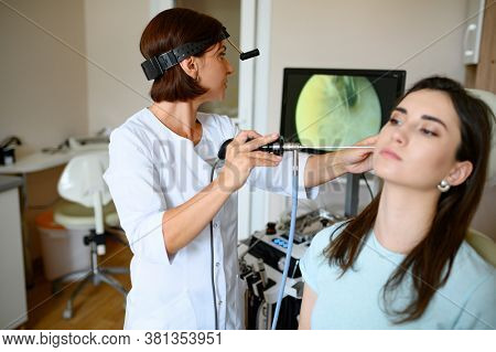 Female ent doctor and patient in chair, otoscope
