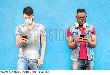 Multiracial Male Friends With Face Masks Using Tracking App With Mobile Smart Phones - Young Milleni