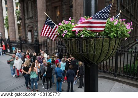 New York, Usa - June 16 2017: American Flags In A Hanging Basket Full Of Petunias In Downtown New Yo
