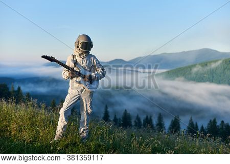 Cosmonaut In Space Suit And Helmet Playing Guitar, Standing On Sunny Green Mountain Glade In Summer,
