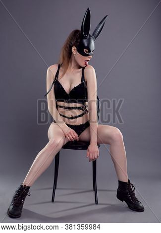 A Sexy Woman In A Black Mask And Underwear Sits Gracefully On A High Chair. Fetish. Photo On A Gray