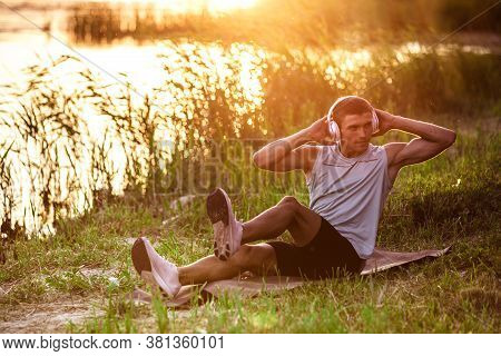 Abs Crunches. A Young Athletic Man Working Out, Training Listening To Music At Riverside Outdoors. C