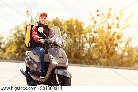 Courier Delivering Food In Yellow Backpack Riding Motorbike Outside In City. Meal Delivering Service