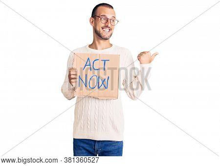Young handsome man holding act now banner pointing thumb up to the side smiling happy with open mouth