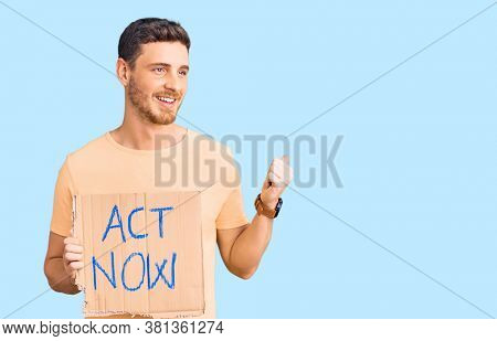 Handsome young man with bear holding act now banner pointing thumb up to the side smiling happy with open mouth
