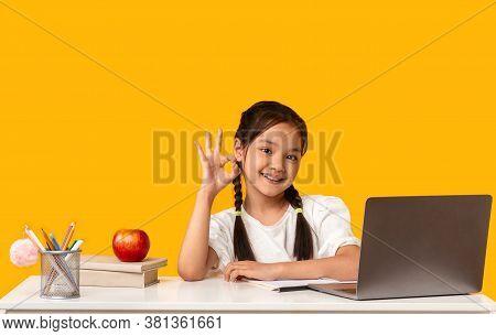 Cheerful Korean School Kid Girl Gesturing Okay Sitting At Desk Doing Homework On Yellow Studio Backg