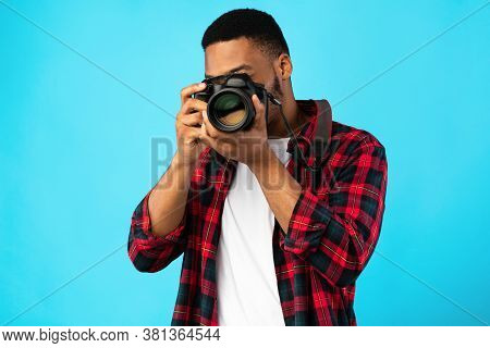 Photography Concept. African American Photographer Man Taking Photo Standing On Blue Background In S