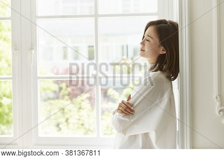 Beautiful Young Asian Woman Standing By Window At Home Arms Crossed Eyes Closed