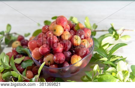 Fruits And Leaves Of Acerola In A Glass Container On A Wooden Surface