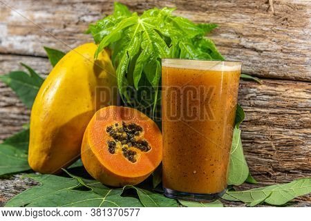 Fruits And Juice Of Carica Papaya Between Papaya Leaves On Wooden Background