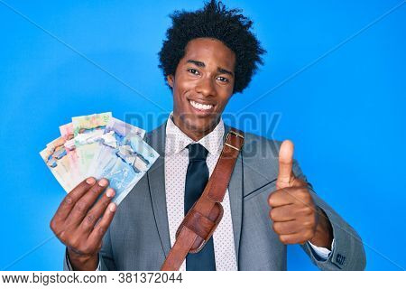 Handsome african american business man with afro hair holding canadian dollars smiling happy and positive, thumb up doing excellent and approval sign