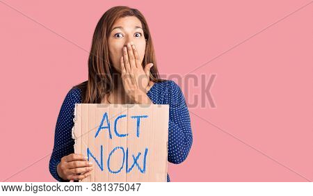 Middle age latin woman holding act now banner covering mouth with hand, shocked and afraid for mistake. surprised expression