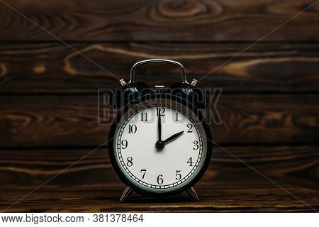 Clock On A Wooden Background. The Clock Shows The Time Of Two O'clock In The Afternoon. Clock Showin