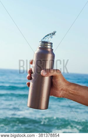 closeup of a man pouring water out of an aluminum reusable water bottle in front of the ocean