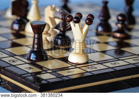 White Queen Embattled By Black Rook And Knight On Chess Board During Chess Gameplay