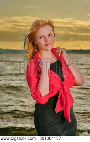 Portrait Of A Young Red-haired Girl On An Evening Walk Along The Seashore. Summer Sunny Evening.
