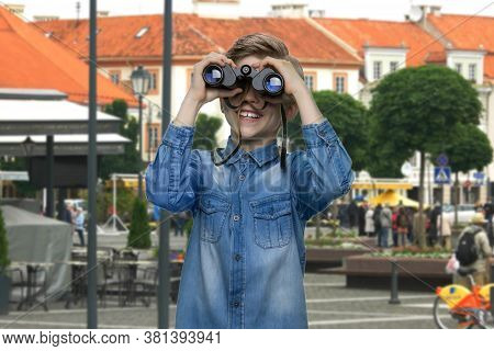 Boy Observing City Using Binoculars. Curious Child In Denim Jacket Exploring The City. Tourism And V