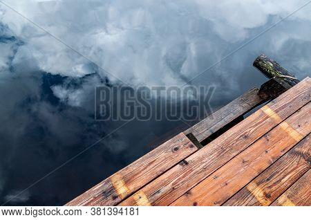 Background With A Wooden Pier And Water With A Reflection Of The Sky And Clouds