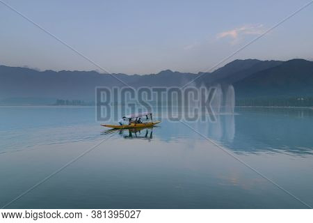 Fountains And Houseboat Over The Dal Lake With Mountains In The Background, At Dusk. Dal Lake Is The
