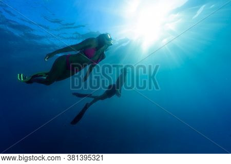 A Young Woman Is Diving In Cristal Water With Mask  And Fins With A Buddy
