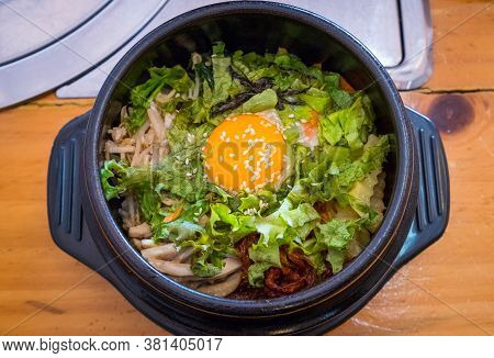 Top View Of Bibimbap, Traditional Korean Food Served In Warm Bowl And Cooked By Mixed Rice With Vege