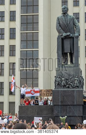 Minsk, Belarus - Aug 14, 2020: Peaceful protest demonstrations at Independence square in Minsk, Belarus. Demonstrators hold national flag near the Lenin monument with Government building at background