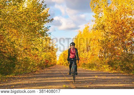 Bike autumn ride woman biking outdoors in fall nature foliage park - bicycle tourism active leisure recreational activity lifestyle people. Girl cyclist.