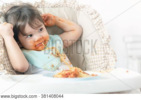 Messy One Year Baby Girl Eating Pasta.  Parents Leave Lovely Infant Girl, Enjoying Eating Meal Alone