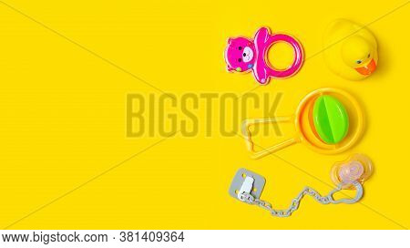 Baby Soother, Rattles, Toys On Yellow Background, Top View