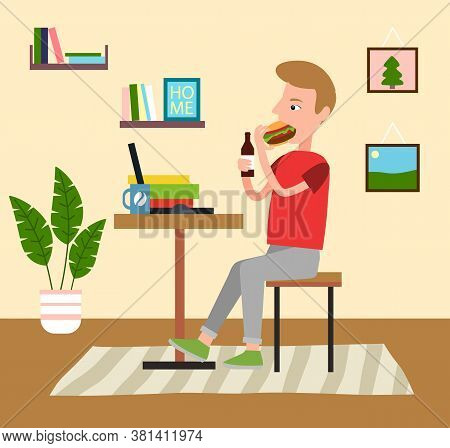 Young Man Sits At A Desk In Front Of A Laptop At His Home. Guy Eats Hamburger And Drinks. Shelf With