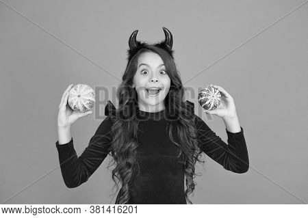 Have Mystery Halloween. Happy Child With Mystery Look. Little Girl In Red Devil Horns Hold Pumpkins.