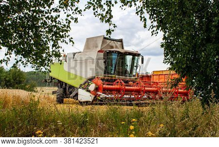 A Beautiful Modern Combine Harvester Stands Between The Foliage Of Trees On A Ripe Wheat Field In Th