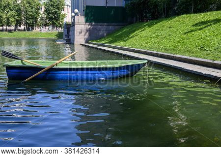 Wooden Boat With Oars On The Water Surface Of The Pond In Sunny Weather. Moscow, Patriarch's Ponds,