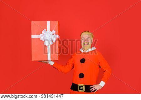 New Year Presents. Santa Delivery Service. Santa Claus With Big Present Box. Smiling Man In Santa Co